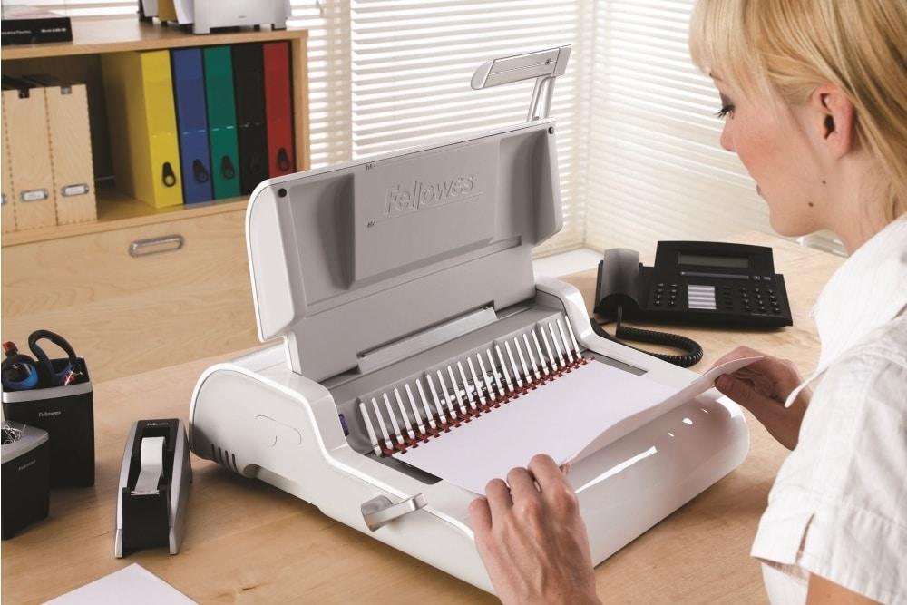 mujer utilizando una encuadernadoras de documentos en casa